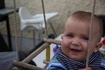 Abbildung: Baby sitzt in einer Schaukel und lacht