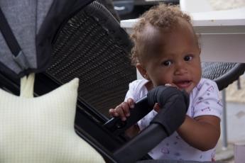 Abbildung: Kleinkind steht neben Kinderwagen